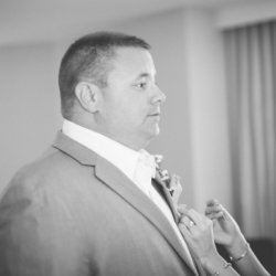 Pinning a boutonniere on the groom