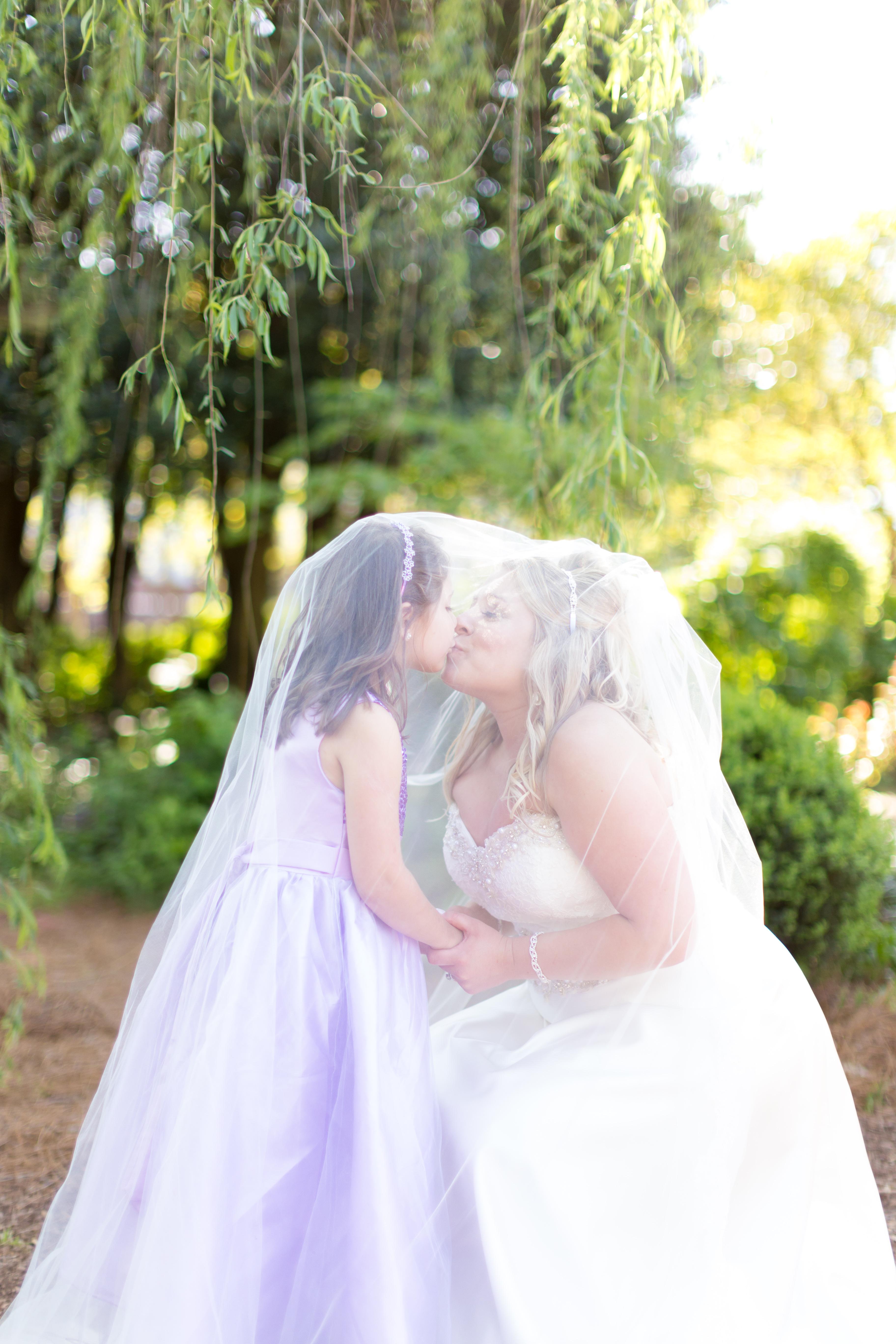 bride kissing the flower girl under her veil