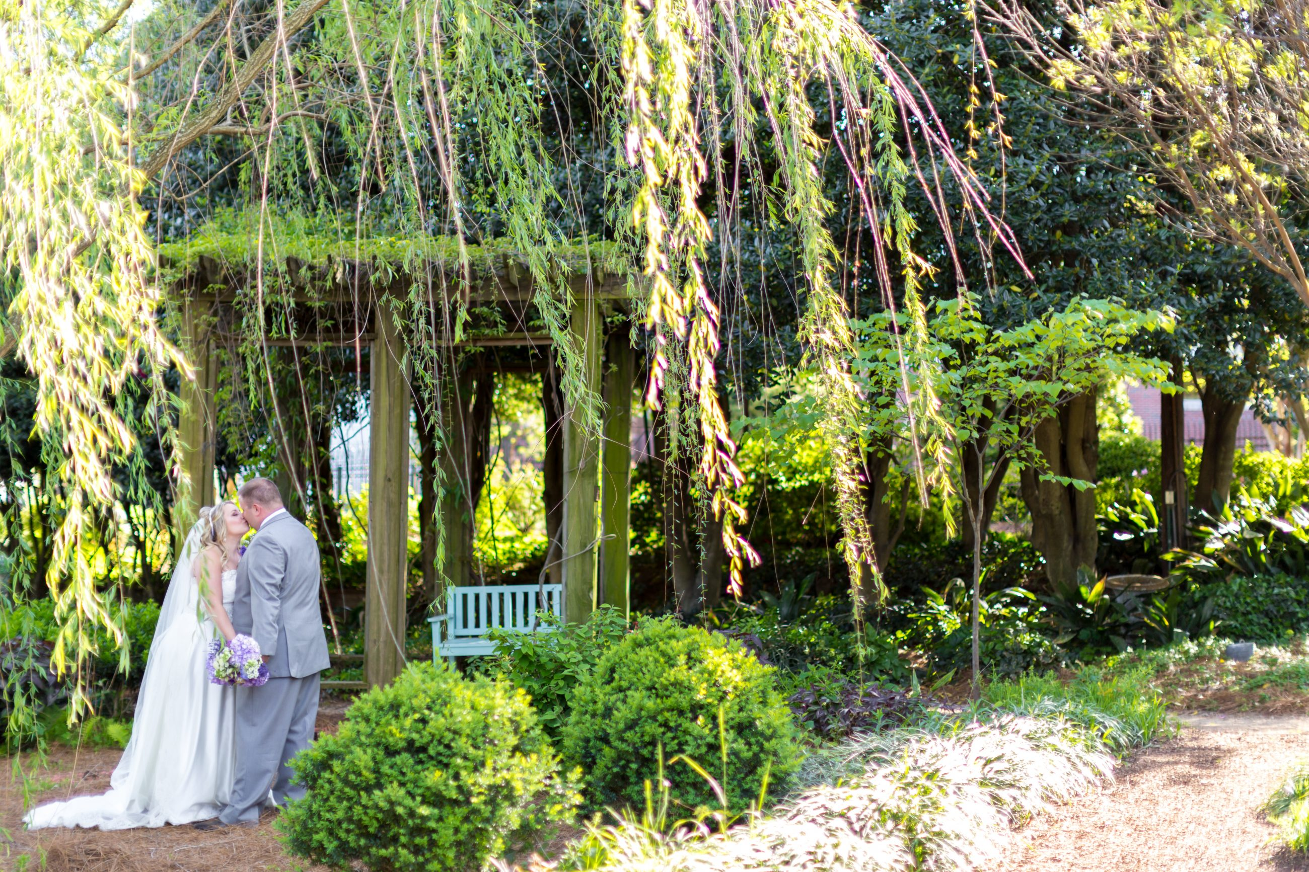 Bride and groom posing for photos at McGill Rose Garden in Charlotte North Carolina photo by Keith Marwitz Photography