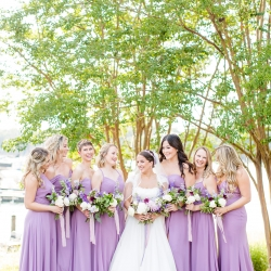 Bride poses with her bridesmaids wearing lavender gowns during her summer wedding on Lake Norman