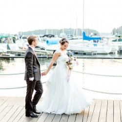 Bride and groom pose among the yachts of Peninsula Yacht Club during their summer wedding coordinated by Magnificent Moments Weddings