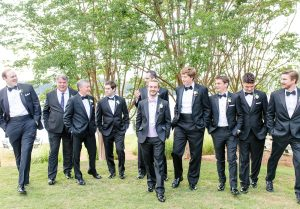 Groom poses with his groomsmen as they prepare for a summer wedding at The Peninsula Yacht Club