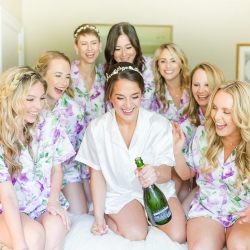 Bride is all smiles as she prepares for her summer wedding with her bridesmaids as the wear matching pajamas and sip champagne
