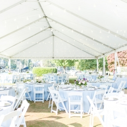A tent from Party Reflections served as the setting for a summer receptions full of pastel blues and lavender flowers at The Peninsula Yacht Club