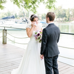 Bride sheds a tear during a heartfelt first look captured by More Beatty Photography for a summer wedding on Lake Norman