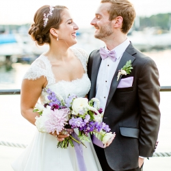 Bride and groom pose on the docks of the Peninsula Yacht Club during their summer wedding featuring soft pastels and lavender accents