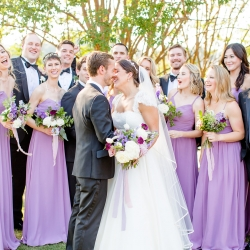 A fun bridal party looks on as a bride and groom exchange a kiss before their wedding at The Peninsula Yacht Club