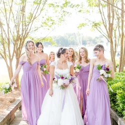 Bride poses with her bridesmaids all wearing soft lavender dresses for a summer wedding coordinated by Magnificent Moments Weddings