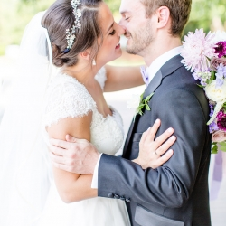 Bride and groom share a kiss as man and wife following their wedding ceremony coordinated by Magnificent Moments Weddings