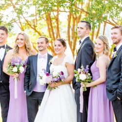 Bride and groom pose with their bridal party during a summer wedding coordinated by Magnificent Moments Weddings