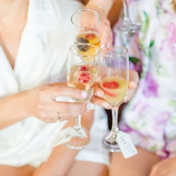 Bride shares a cocktail with her bridesmaids as they prepare for their summer wedding at The Peninsula Yacht Club coordinated by Magnificent Moments Weddings