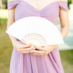 Bridesmaids wore soft lavender dresses and used delicate fans to beat the heat during a summer wedding at The Peninsula Yacht Club