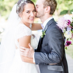 Groom kisses his sweet bride before their lake wedding coordinated by Magnificent Moments Weddings