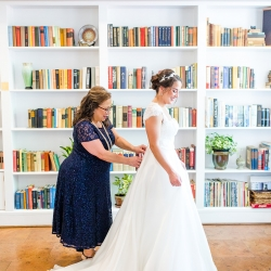 Brides mother helps button her dress as she prepares for her wedding ceremony coordinated by Magnificent Moments Weddings at The Peninsula Yacht Club
