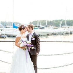 Bride and groom pose for a stunning photo captured by More Beatty Photography among the boats of Peninsula Yacht Club