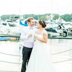 Bride and groom share a cocktail on the docks of the Peninsula Yacht Club during their summer wedding coordinated by Magnificent Moments Weddings