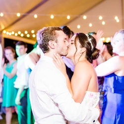 Bride and groom share a kiss on the dance floor during their summer wedding at The Peninsula Yacht Club