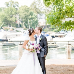 Bride and groom share a kiss during their lake wedding coordinated by Magnificent Moments Weddings