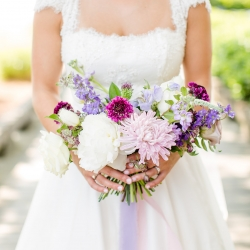 Bride holds a stunning bouquet featuring various shades of purple and lavender for a summer wedding coordinated by Magnificent Moments Weddings