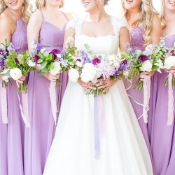Bride and bridesmaids show off their stunning bouquets featuring lavender flowers created by Springvine for a summer wedding off Lake Norman