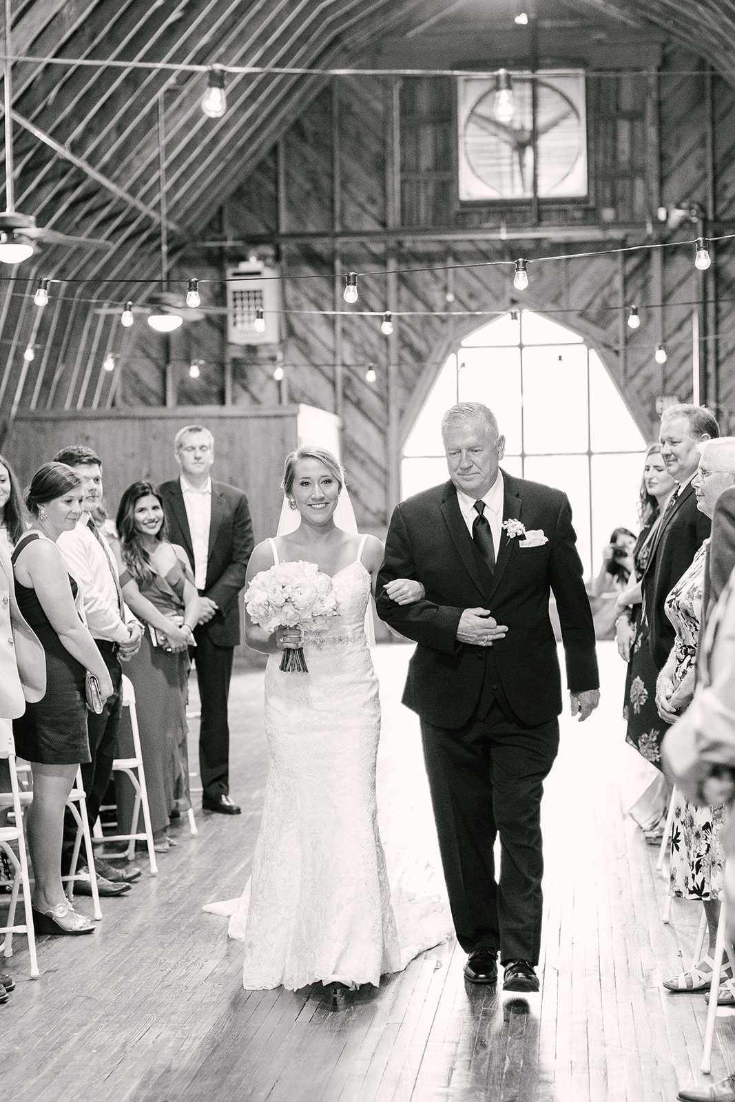 Bride is escorted down the aisle by her father to her spring ceremony at The Diary Barn coordinated by Magnificent Moments Weddings