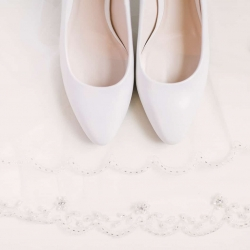 Detail shot of bridal veil and shoes captured by Paige Ryan Photography for a spring wedding at The Diary Barn