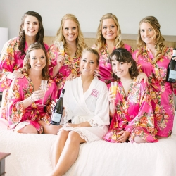 Bride poses with her bridesmaids in their matching silk floral robes as they prepare for their Dairy Barn wedding that is captured by Paige Ryan Photography