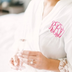 Bride shows off her custom monogrammed robe as she gets ready for her spring wedding at The Diary Barn coordinated by Magnificent Moments Weddings