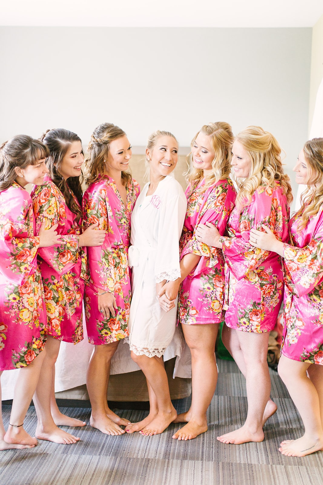 Bride poses with her bridesmaids in matching floral robes as they prepare for their spring wedding at The Diary Barn