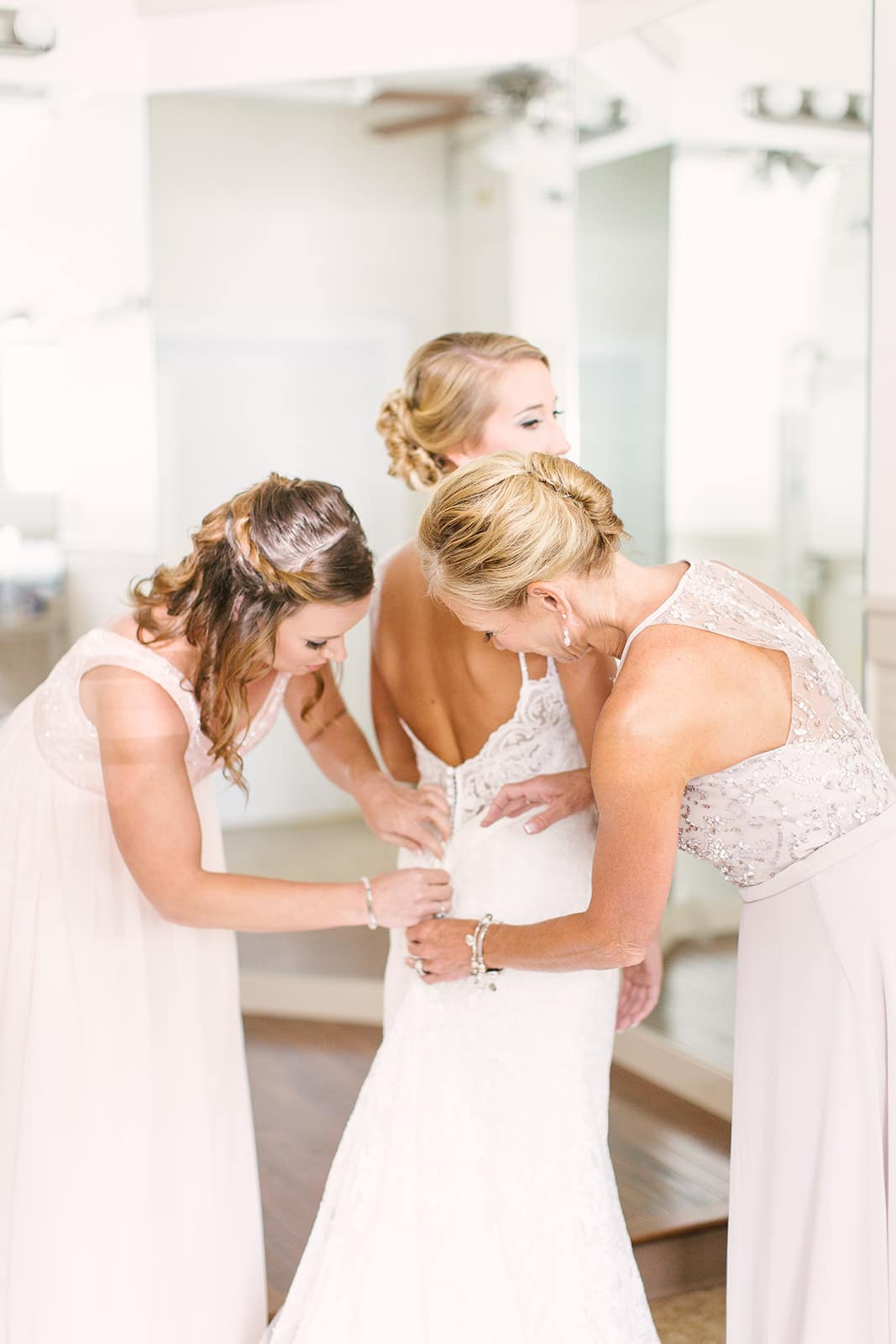 Bride gets dressed in her beautiful gown before her wedding at The Diary Barn which was coordinated by Magnificent Moments Weddings