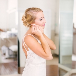 Bride prepares for her wedding by placing on jewelry as she is captured by Paige Ryan Photography
