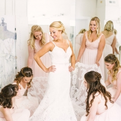 Bridesmaids assist the bride in putting on her gown as she prepares for her spring wedding at The Diary Barn captured by Paige Ryan Photography