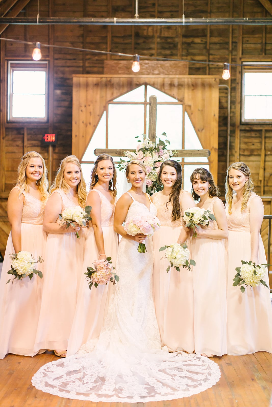 Bride poses with her bridesmaids before her ceremony at The Diary Barn image captured by Paige Ryan Photography