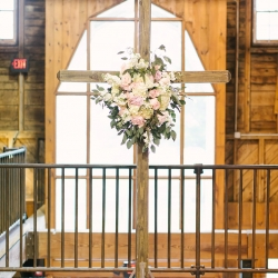 Cross backdrop for a Dairy Barn ceremony featuring stunning flowers by Charlotte Flower Market and coordinated by Magnificent Moments Weddings