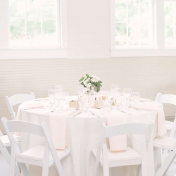 Magnificent Moments Weddings coordinated a spring wedding at the Diary Barn featuring white linens, pale pink napkins, and simple hydrangea centerpieces