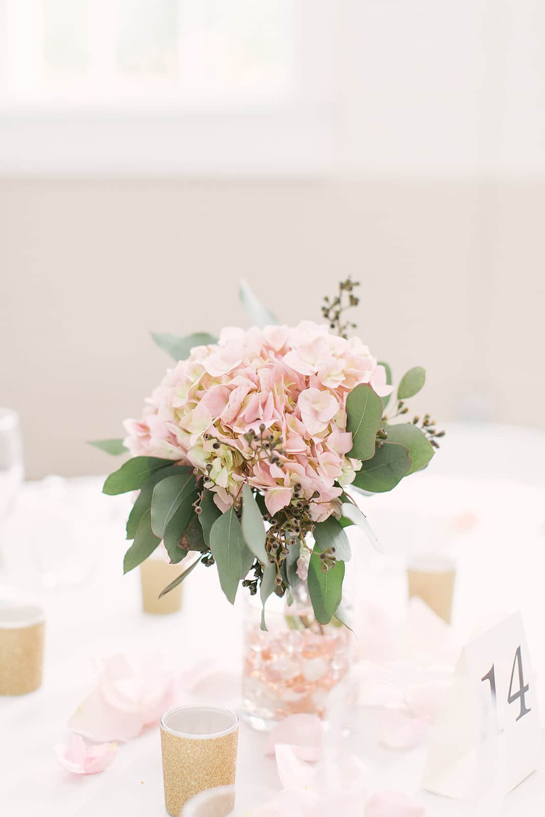 Pale pink hydrangeas serve as centerpieces for a spring wedding at The Diary Barn captured by Paige Ryan Photography