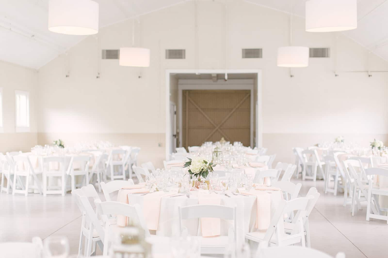 Reception space for a spring wedding at The Diary Barn features white linens, pale pink napkins, and white rose centerpieces all coordinated by Magnificent Moments Weddings