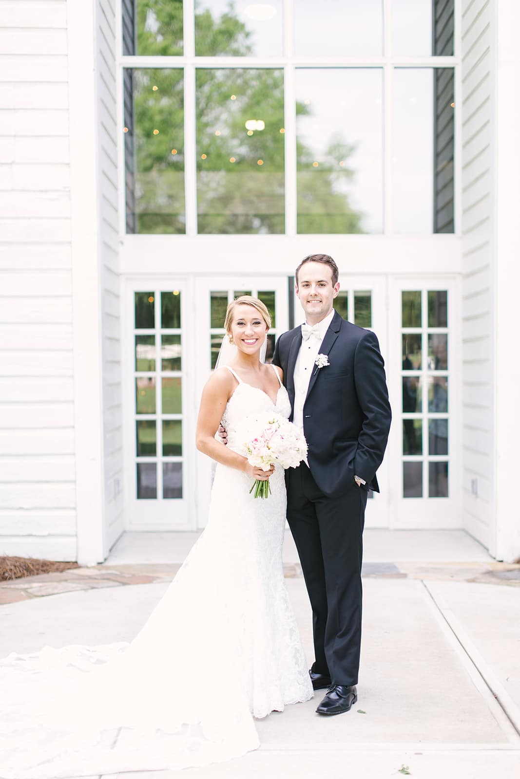 Bride and groom pose in front of a large glass window at The Diary Barn captured by Paige Ryan Photography