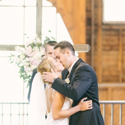 Bride and groom share a kiss to seal their spring ceremony at the Diary Barn captured by Paige Ryan Photography