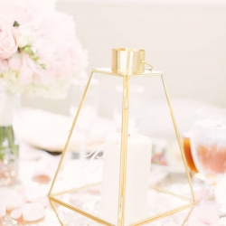 Gold lantern centerpieces set atop gold sequin linens sprinkled with white rose petals create a romantic setting at a spring wedding at the Diary Barn captured by Paige Ryan Photography