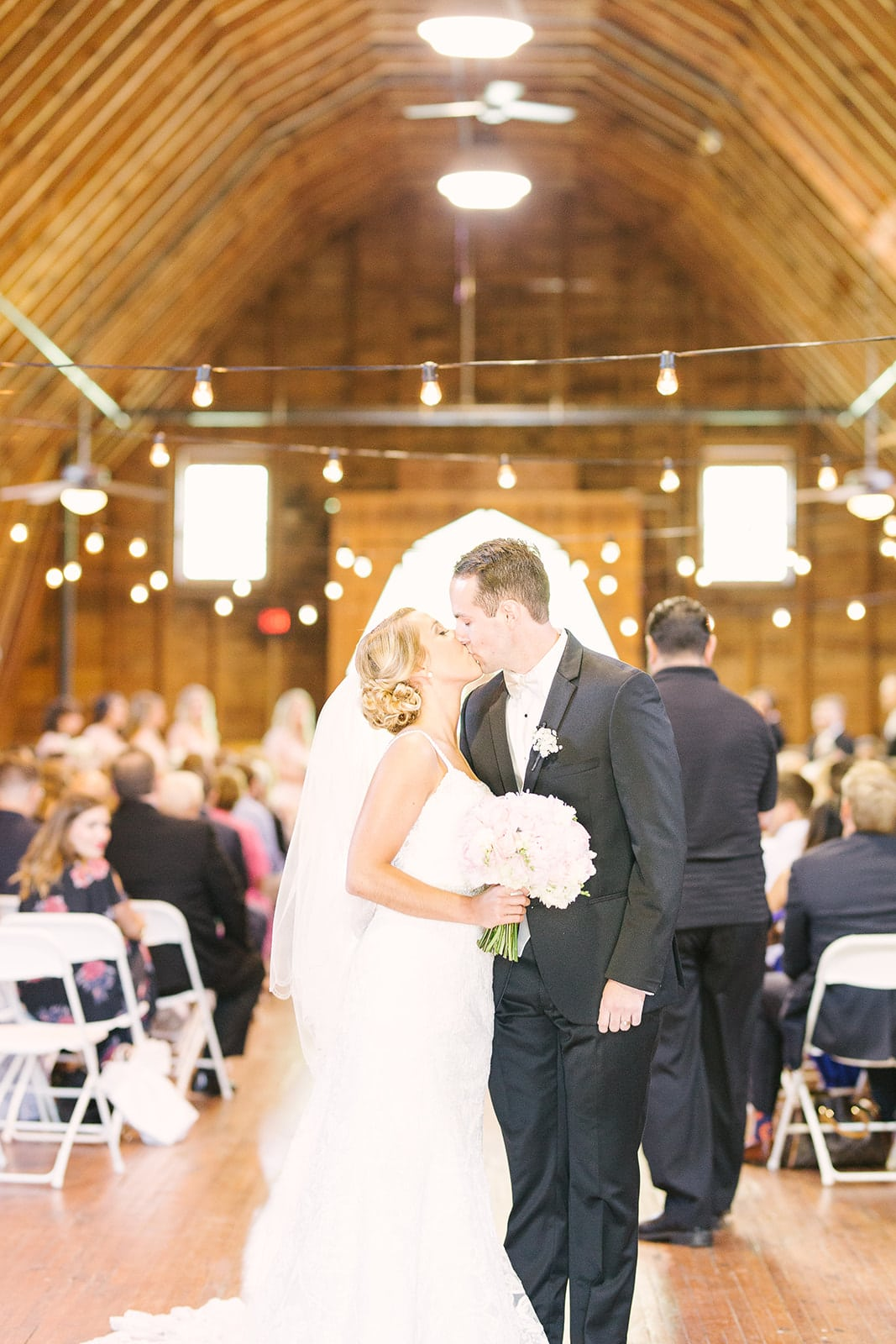 Bride and groom share a kiss following their spring wedding ceremony at The Diary Barn coordinated by Magnificent Moments Weddings