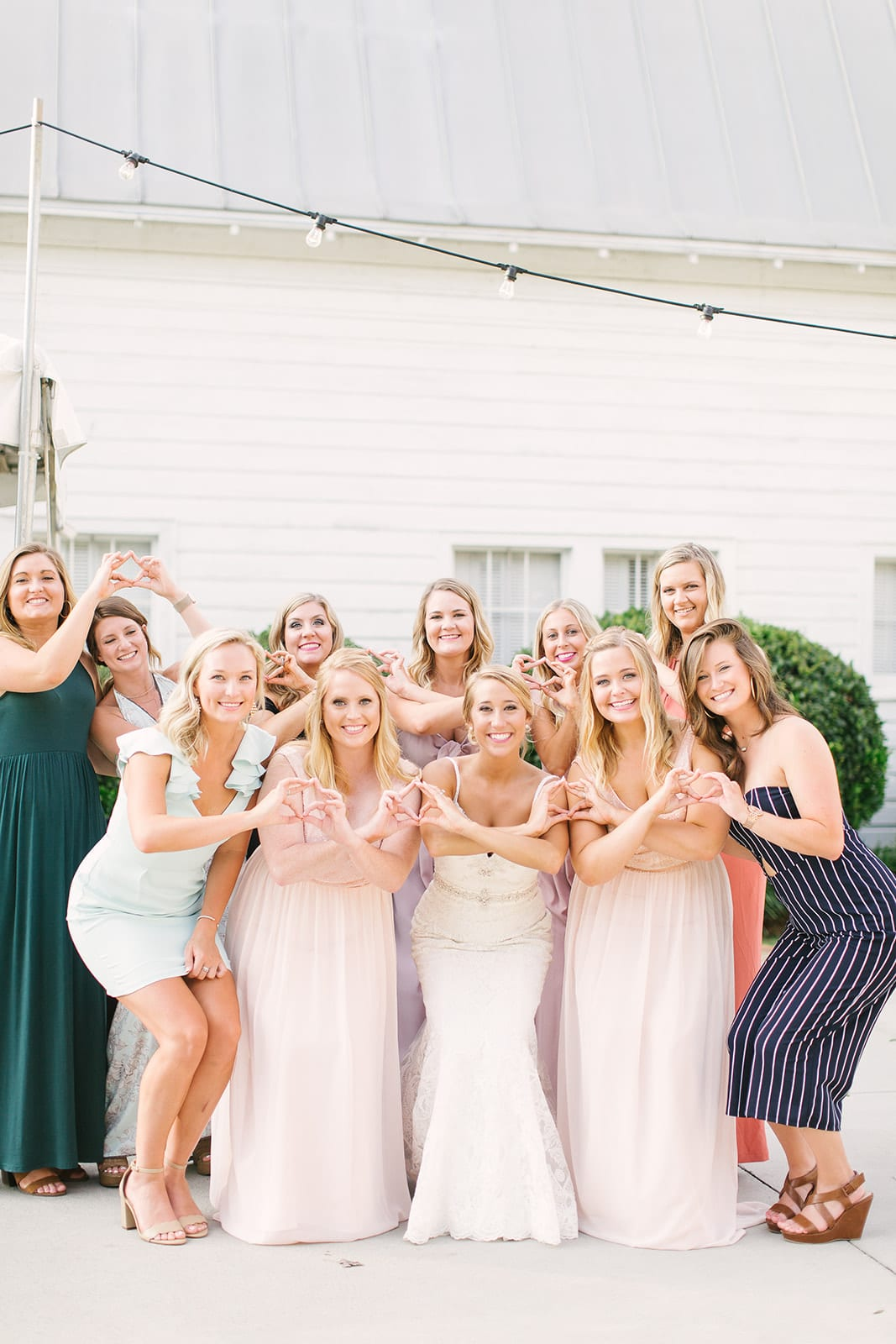 Bride poses with her sorority sisters during cocktail hour at her spring Dairy Barn wedding which was coordinated by Magnificent Moments Weddings