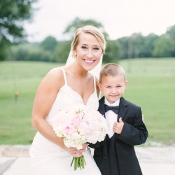 Bride poses with ring bearer for a fun picture captured by Paige Ryan Photography