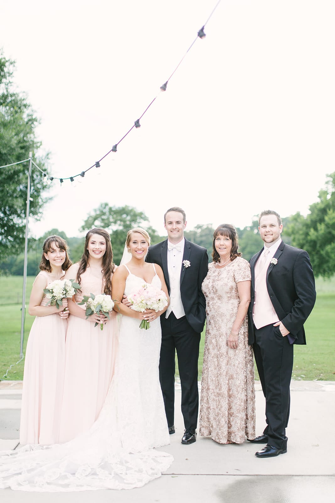 Bride and groom pose with family before their spring wedding coordinated by Magnificent Moments Weddings at The Diary Barn