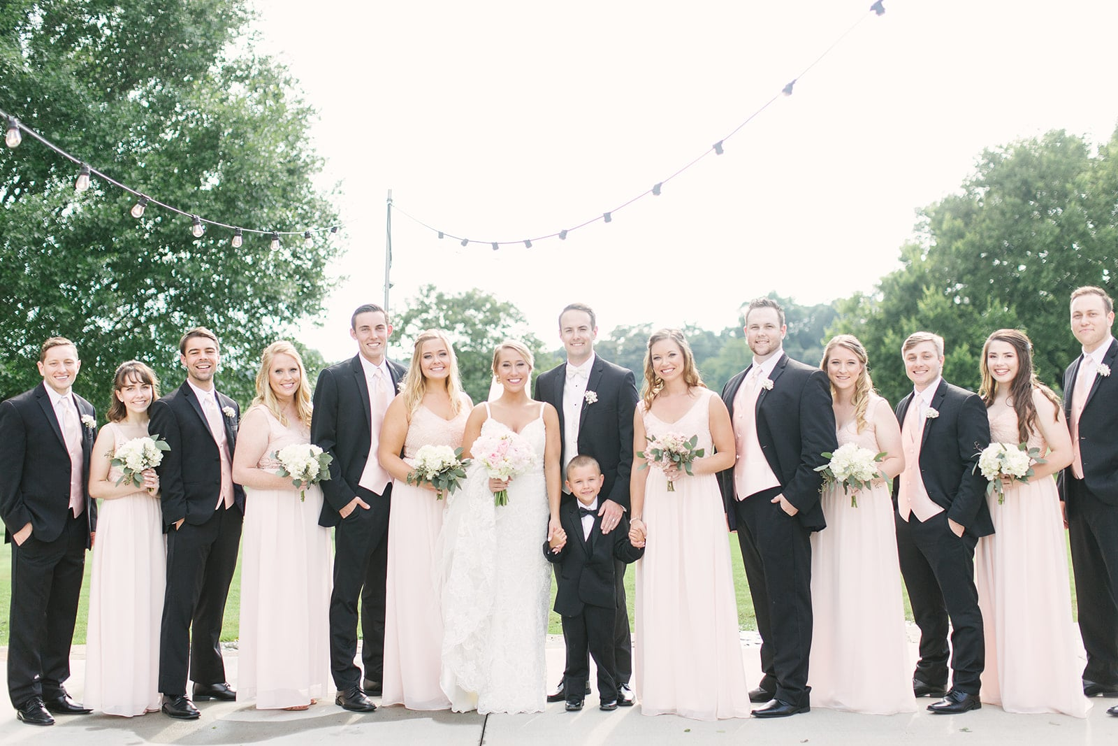 Paige Ryan Photography captures the bride and groom with their bridal party before their spring wedding at The Diary Barn