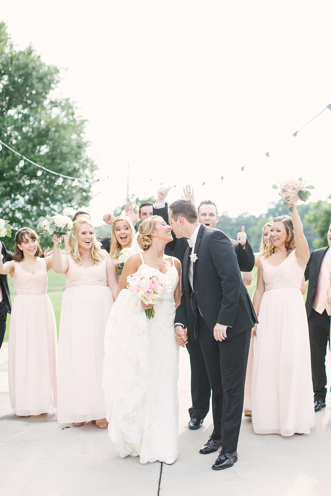 Bride and groom share a kiss as their bridal party looks on before their spring ceremony at The Diary Barn coordinated by Magnificent Moments Weddings