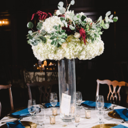 White hydrangea centerpieces with maroon and greenery accents by Magnificent Moments Weddings