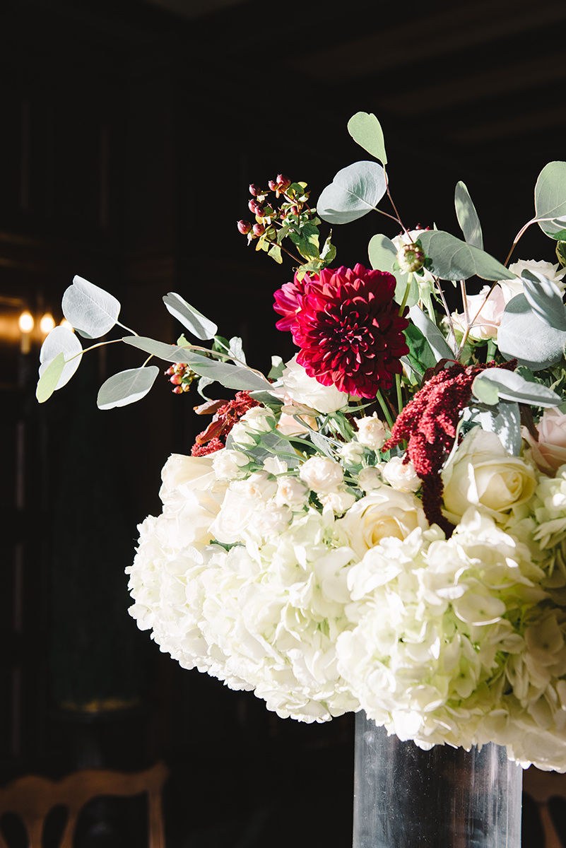 Tall vase centerpieces white hydrengeas roses and maroon accent flowers photography by Riette Farthing Photography