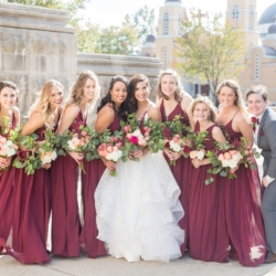 Bride with bridesmaids in wine colored dresses with gold sashes holding bouquets designed by Magnificent Moments weddings and captured by Ryan and Alyssa Photography
