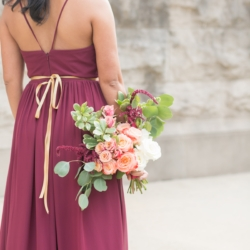 Bridesmaid wearing wine colored dress with gold ribbon sash holding hand tied bouquet full of pink roses accent with deep wine colored flowers and greenery for Charlotte North Carolina uptown wedding